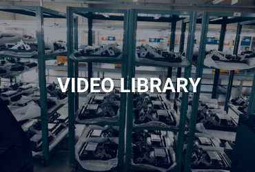 """The words """"Video Library"""" are across the image in white. There are shelves lining the photo. The shelves have various ATM parts on them, such as printers, cash cassettes, and more."""