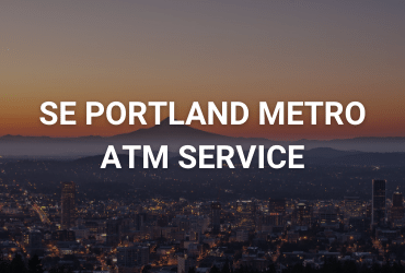 """The words """"South East Portland Metro ATM Service"""" are across the image in white. An orange sunset falls on a mountain overlooking a glowing town."""