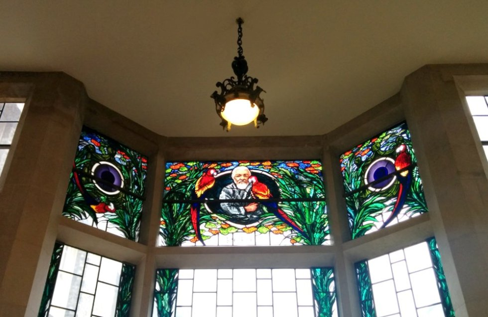 Stained glass window featuring Edward James and parrots. Underneath is the word 'poeta' (not visible in this overexposed picture)