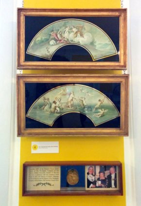 Framed fan leaves (paintings unmounted and unpleated) above a photograph of Hélène Alexander receiving a gold medal from The Worshipful Company of Fan Makers