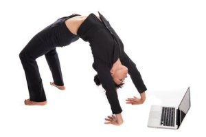 Suited Woman In Yoga Pose working with Laptop