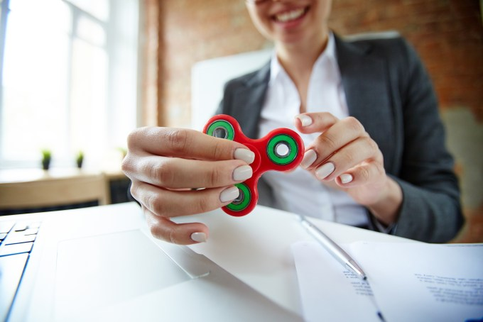 employee at desk playing with fidget spinner