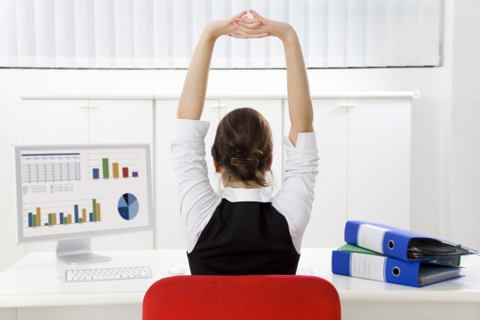 employee stretching hands above head to relieve back pain from hunching