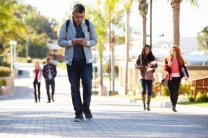 person walking while looking at smartphone