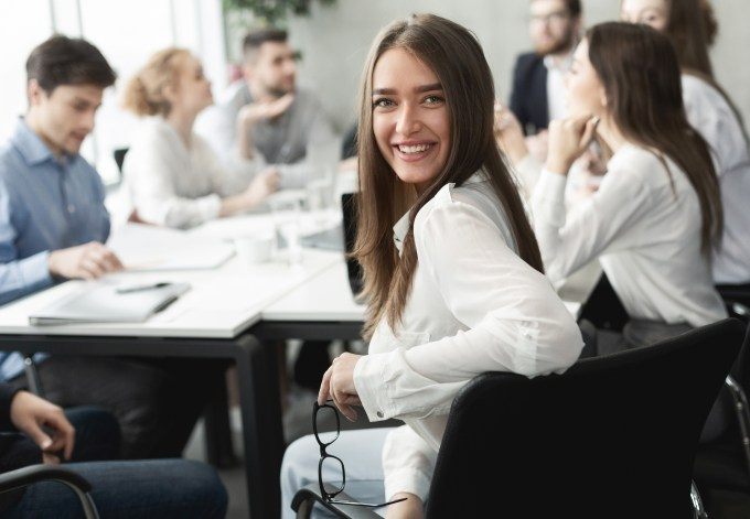 Happy business lady smiling to camera during meeting, colleagues working on background