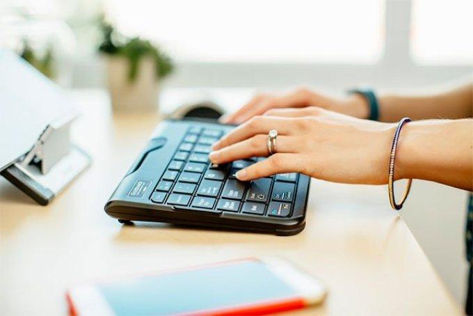 woman typing ergonomic at keyboard