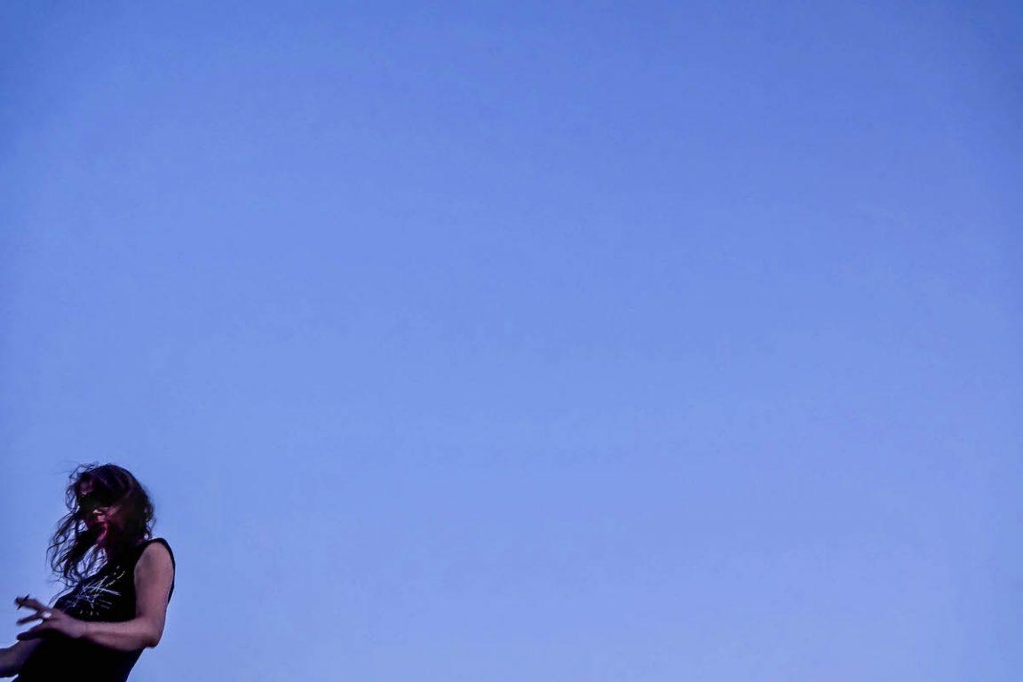 Muzikante Onrust links onderaan tegen een blauwe hemel