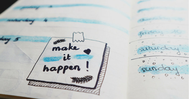 """Close up of notebook with note reading """"make it happen"""""""