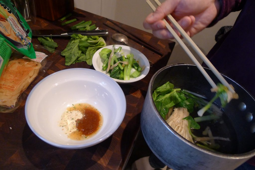 """Melting"" the flavouring sachets and taking the greens and mushrooms from the broth pot."