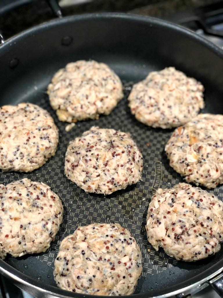 Salmon burger patties cooking in frying pan