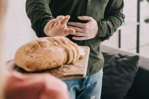 Man saying no to bread for What Causes Celiac Disease header