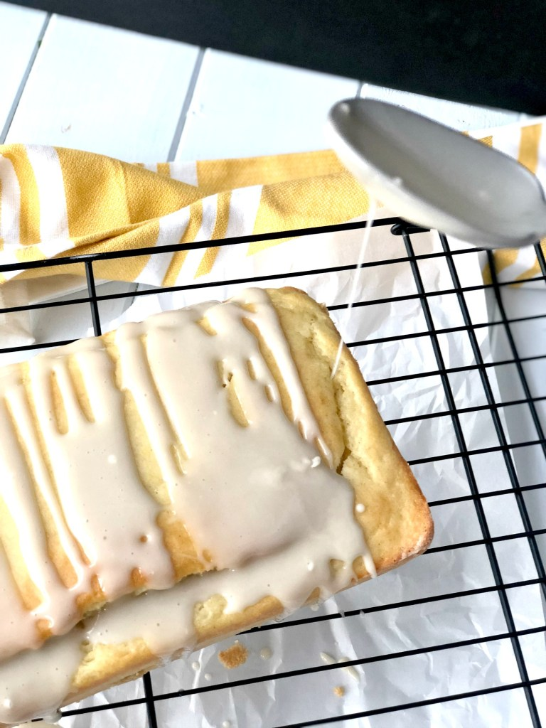 Drizzling icing atop gluten-free lemon vanilla pound cake