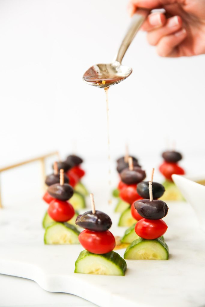 Drizzling Greek dressing over Greek Salad Kabobs