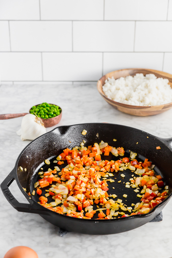 diced carrots and onions sauteing in a pan