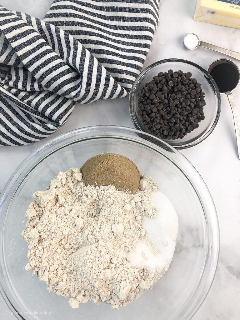a bowl with oat flour, sugar and salt ready to be made in to gluten-free chocolate chip cookie dough balls