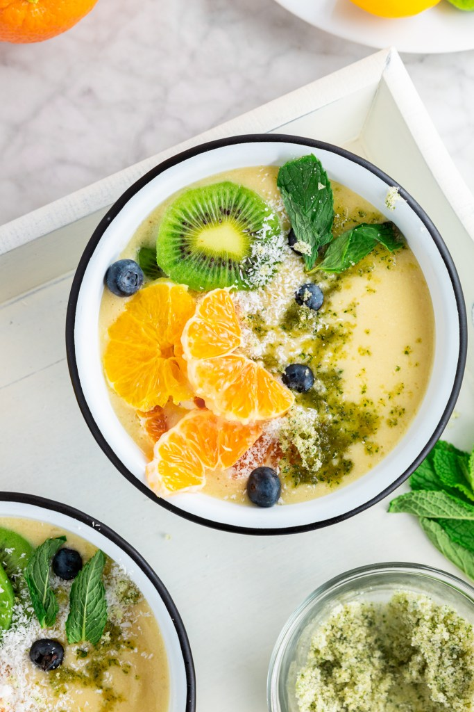picture of tropical smoothie bowl topped with mint, kiwi, and oranges
