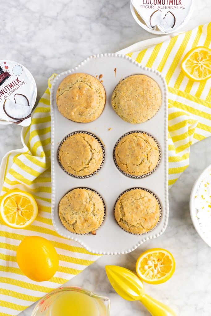 Picture of cooked gluten-free lemon poppy seed muffins with lemons and So Delicious coconutmilk yogurt alternative in picture.