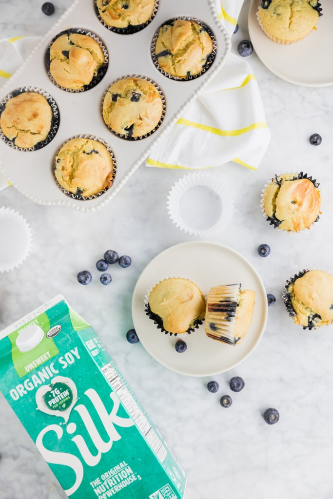 Overhead shot of gluten-free blueberry muffins in muffin tin, outside of muffin tin and Silk soymilk