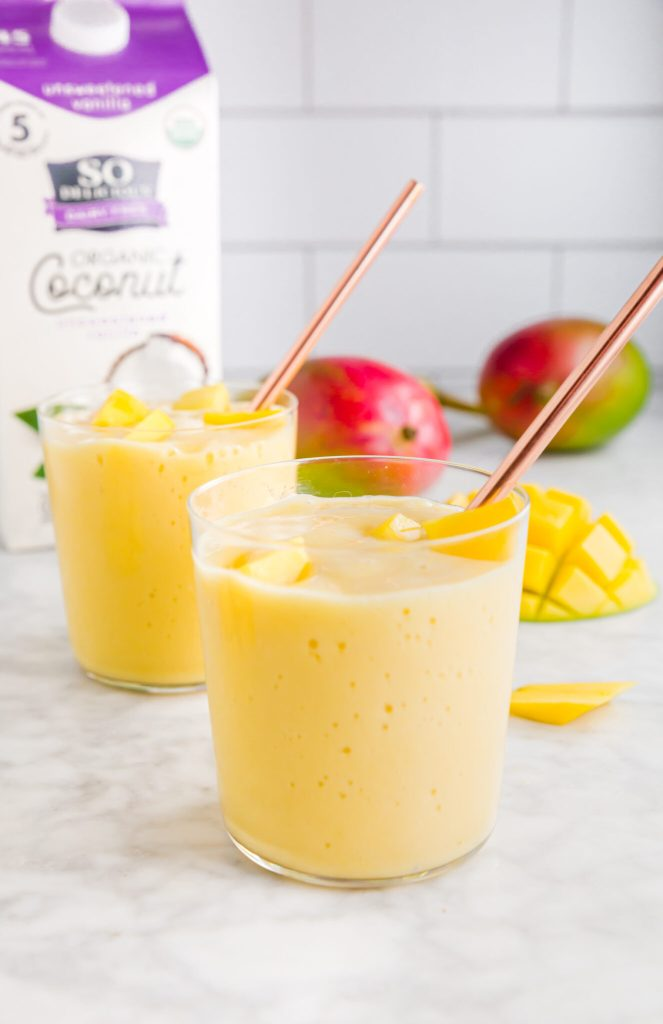 Two tropical mango-coconut smoothies in front of picture with So Delicious coconutmilk and fresh mangoes in the back of the picture.
