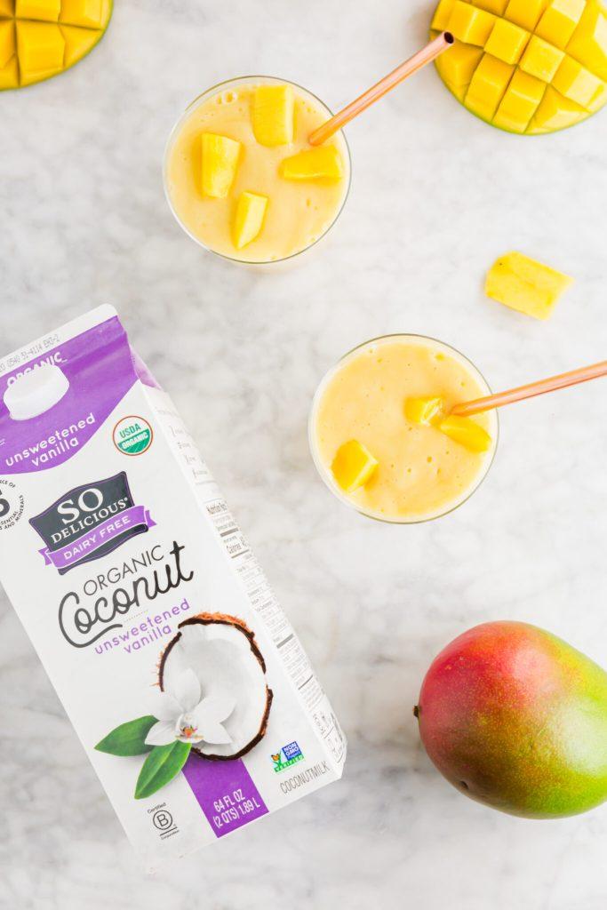 Two tropical mango coconutmilk smoothies with So Delicious dairy free coconutmilk carton