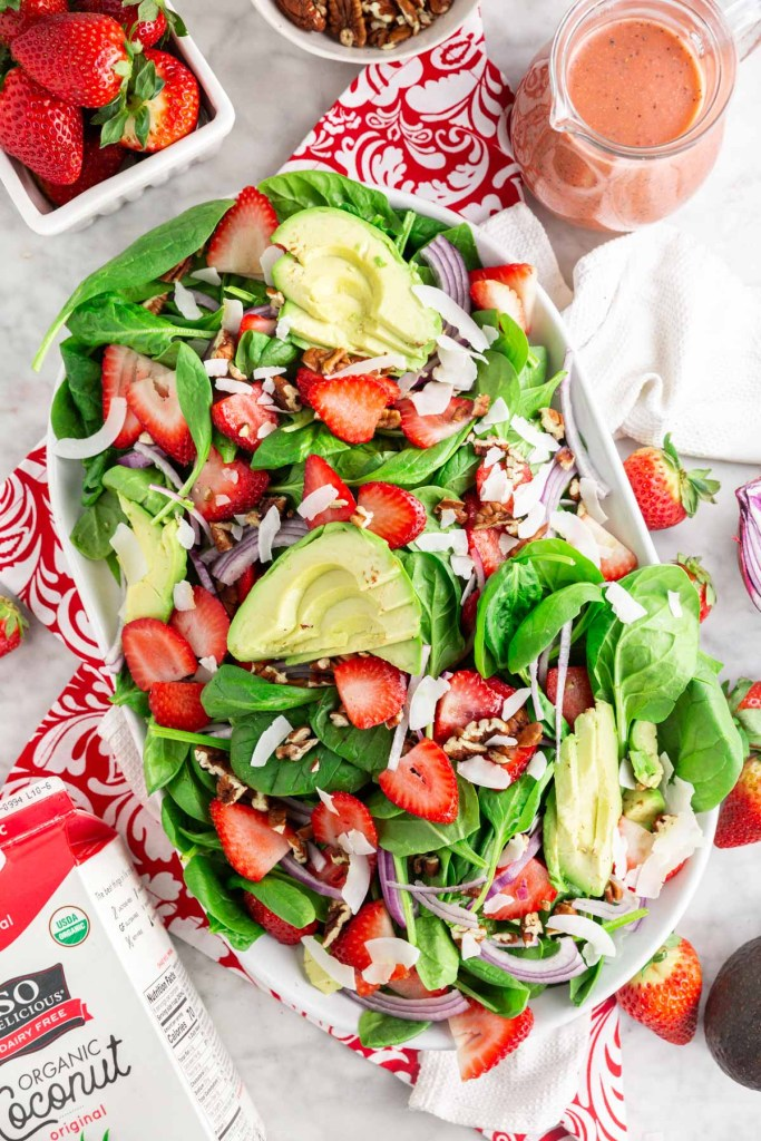 Overhead shot of salad with spinach, strawberries, avocado, pecans and coconut shreds
