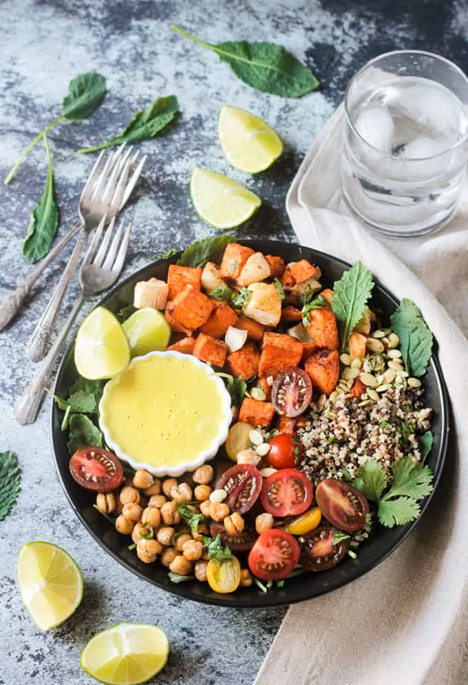 Bowl featuring sweet potatoes, quinoa, chickpeas, tomatoes and a white cashew sauce.
