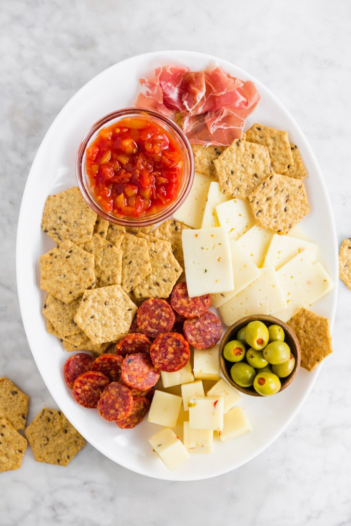 Overhead picture of an oval snack board with spicy deli meats, crackers, cheeses and olives.