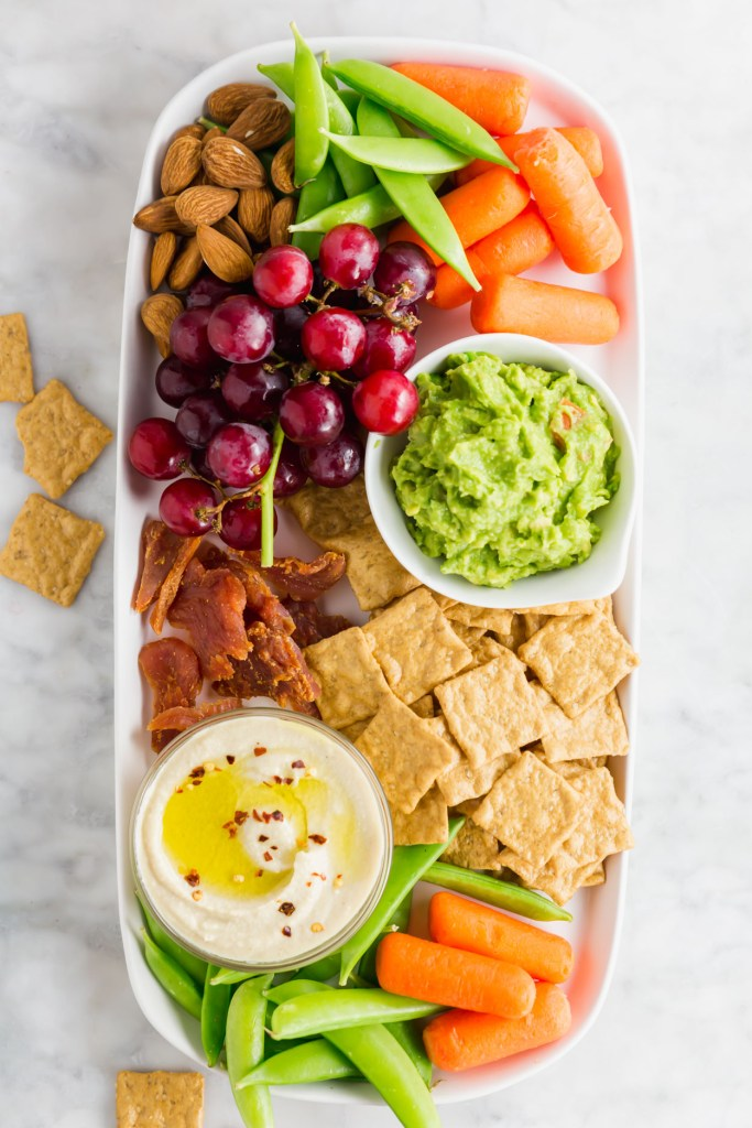 Kid friendly snack board with vegetables, fruits and guac.