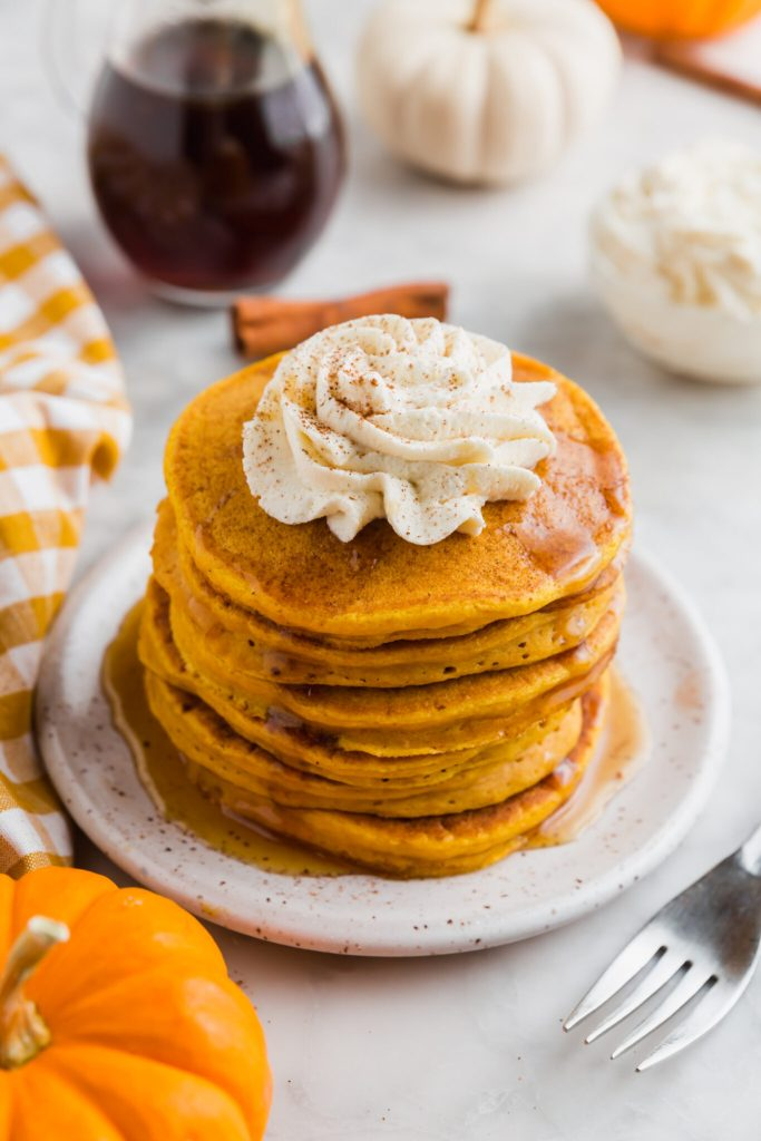 Stack of pumpkin pancakes topped with whipped cream and cinnamon.