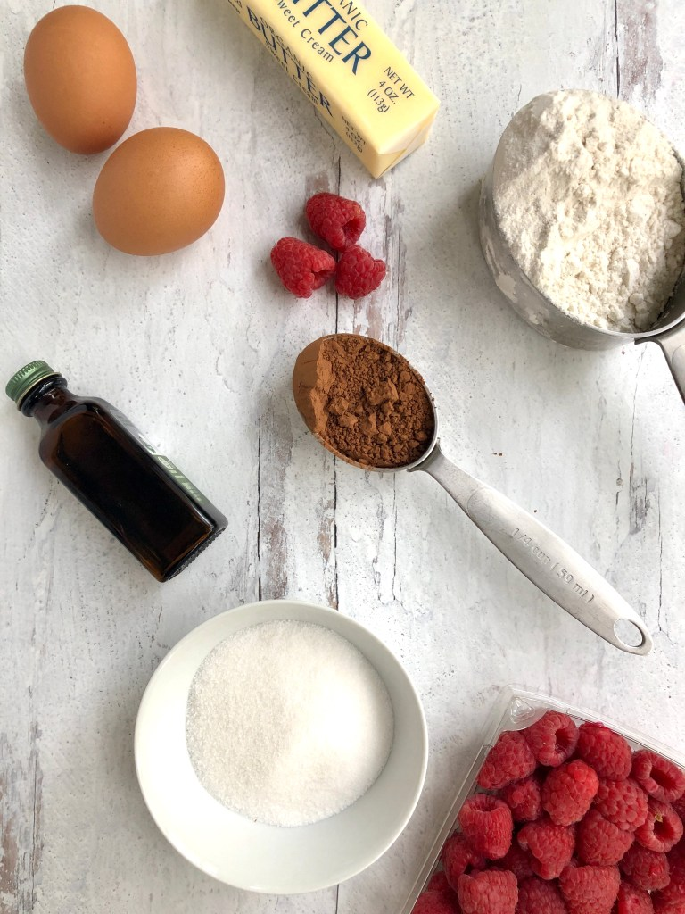 Overhead picture of ingredients needed to make the cupcakes including eggs, butter, vanilla, flour, sugar and cocoa