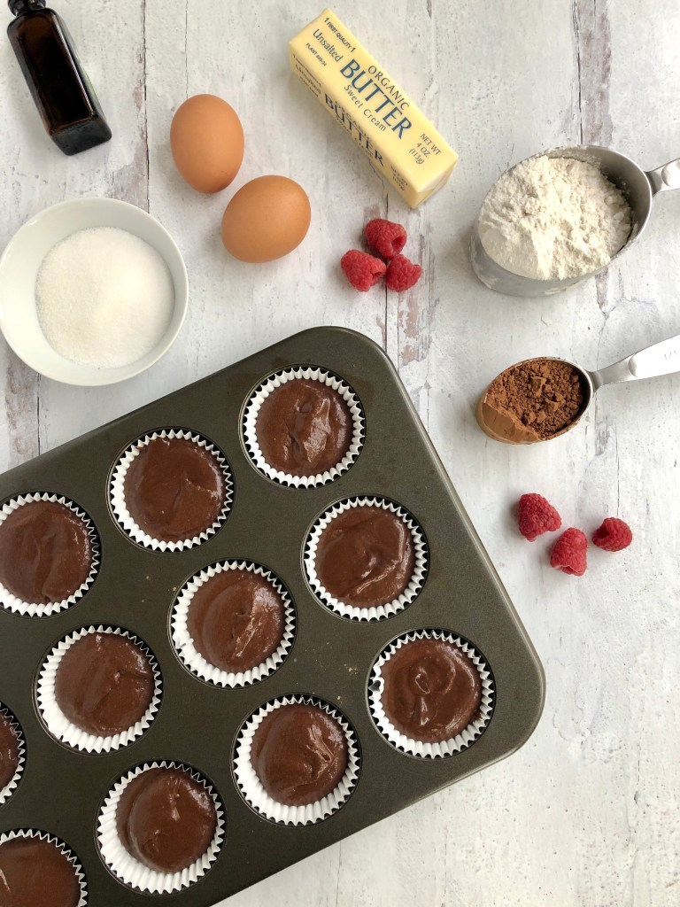 Picture of cupcake tins filled with batter and ready for baking. The picture also shows flour, butter, eggs, and raspberries