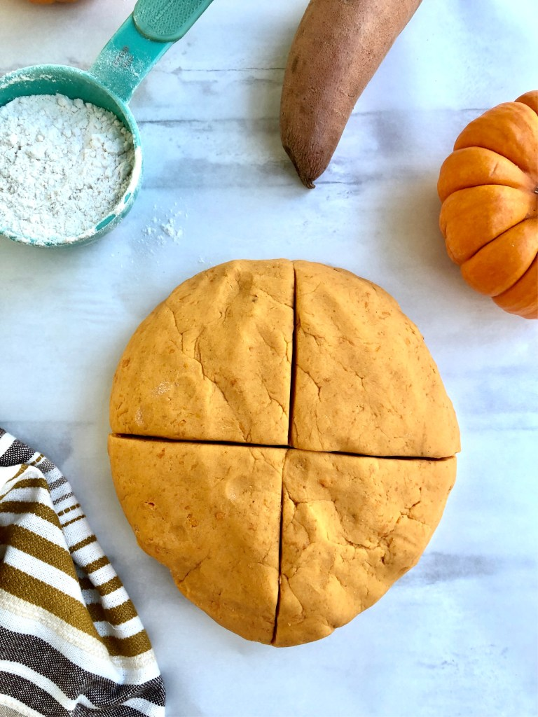 Picture of round ball of gnocchi dough cut into four sections.
