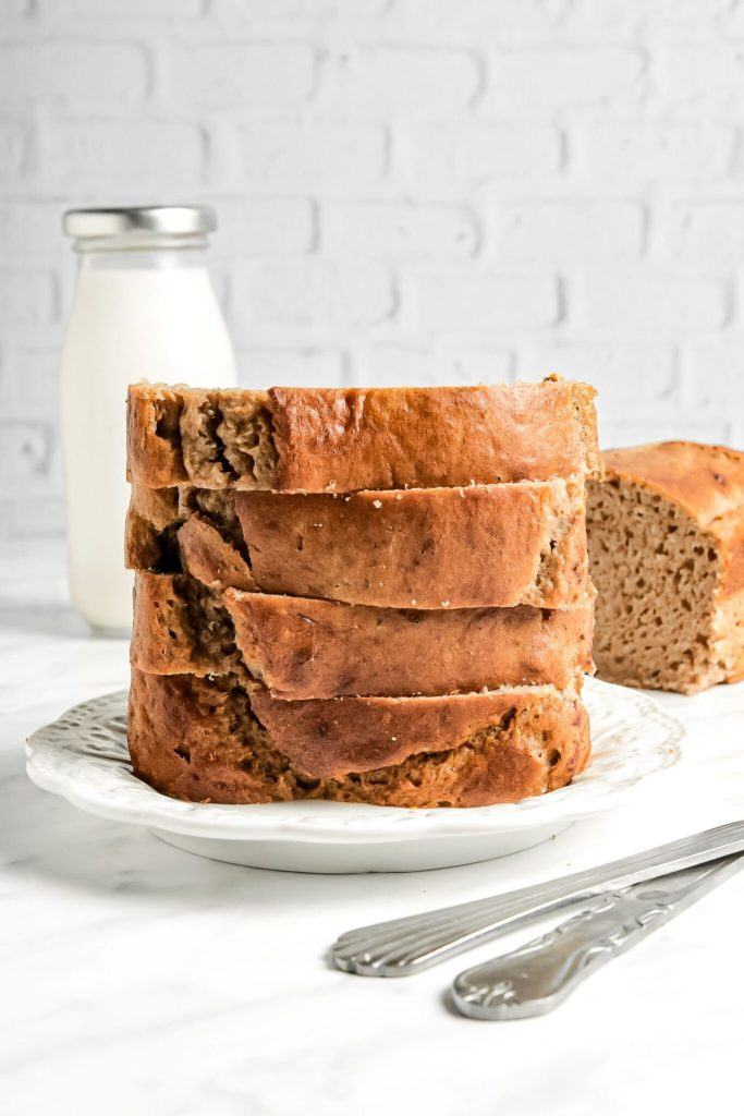 Large stack of banana bread slices with milk in background.