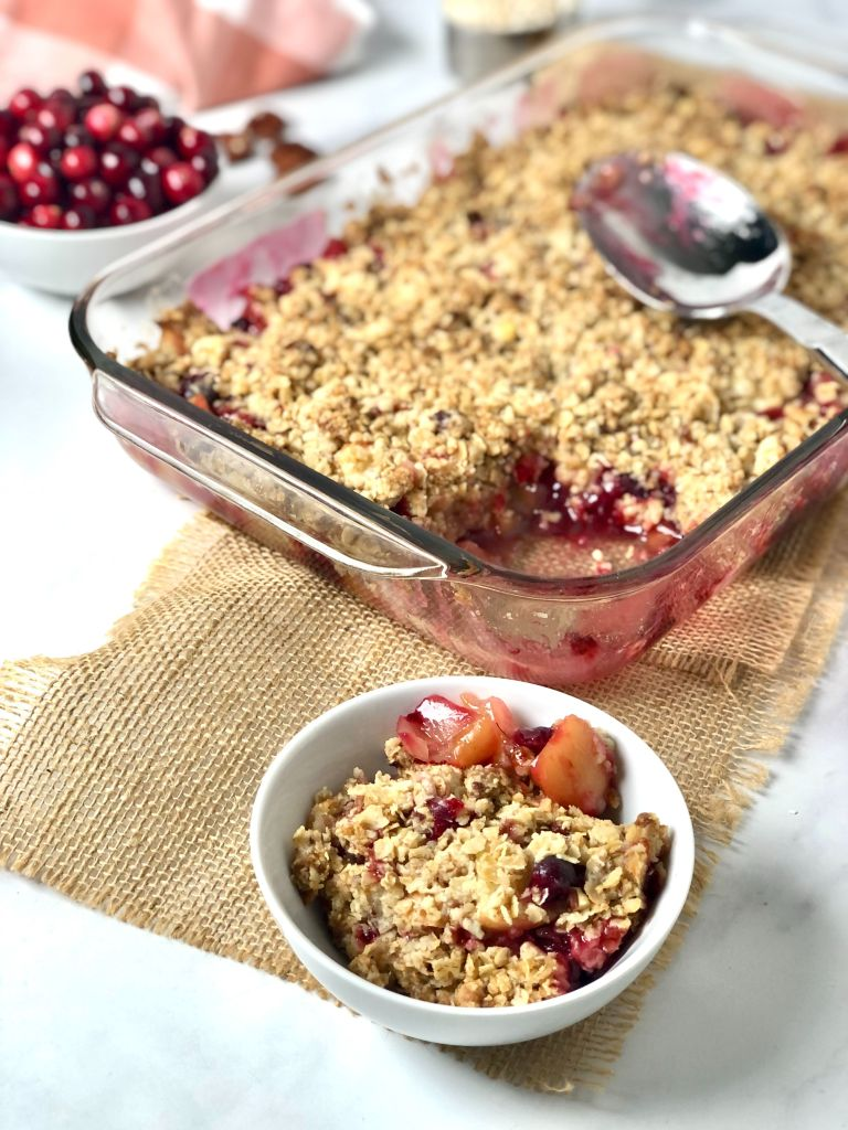 Image of a bowl of the apple cranberry crisp with the casserole in the background