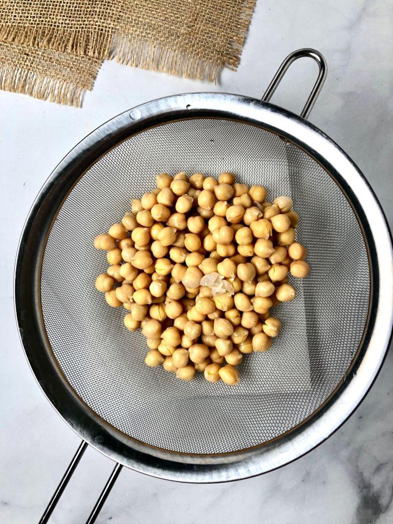 Picture of garbanzo beans in a strainer and the skins coming off of some of them.