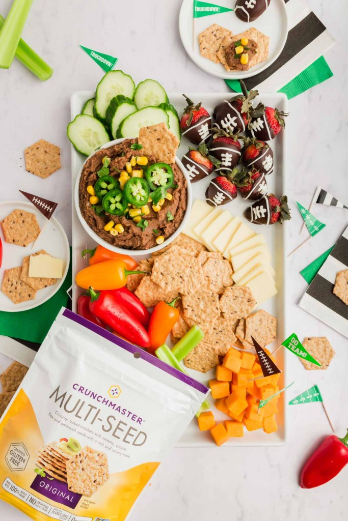 Overhead shot of official game day snack board and package of Crunchmaster crackers