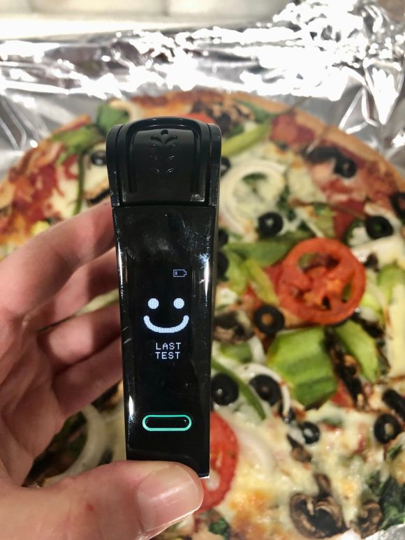 Picture of smiling face on Nima Sensor over Mellow Mushroom gluten-free pizza pie