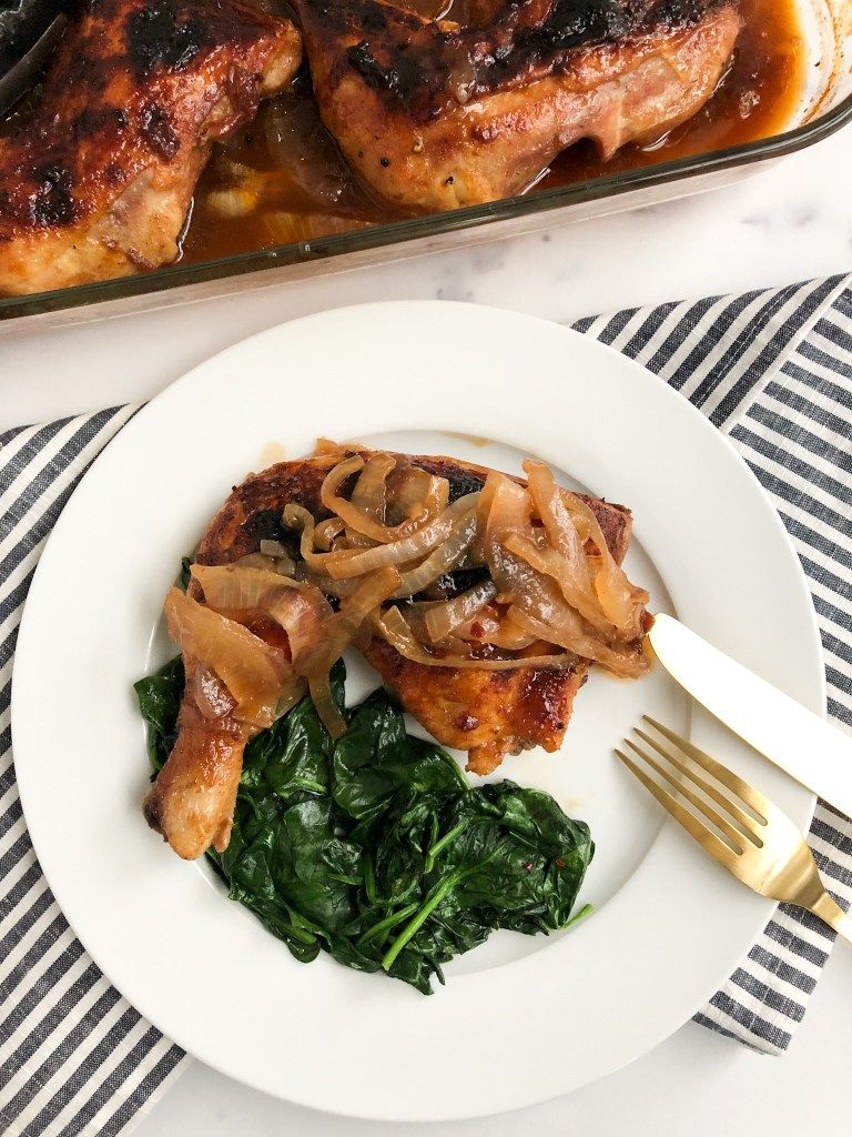 Picture of plated BBQ Coke Chicken with onions on top and served with spinach