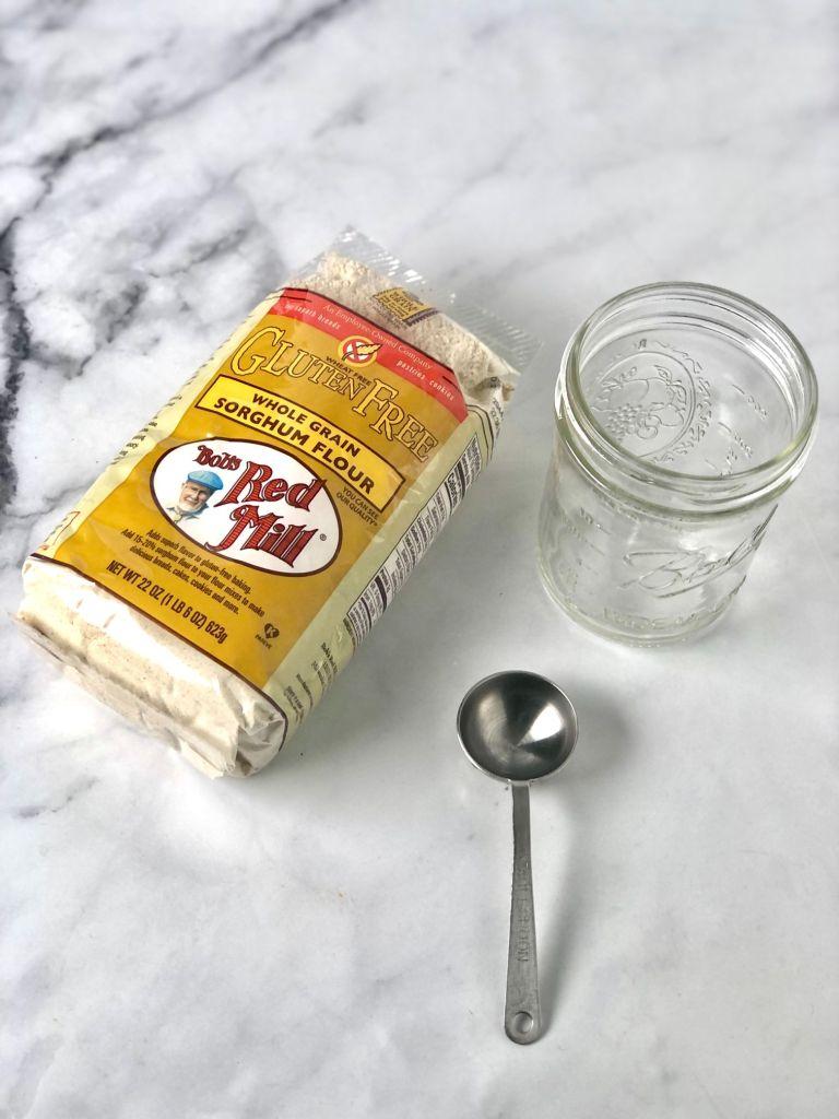 mason jar, sorghum flour and tablespoon on a table.
