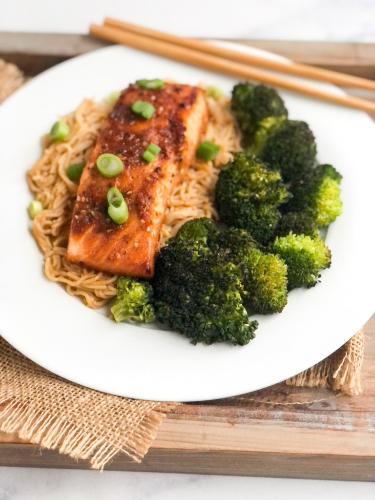 Cooked Asian salmon on top of rice ramen and served with a side of broccoli.