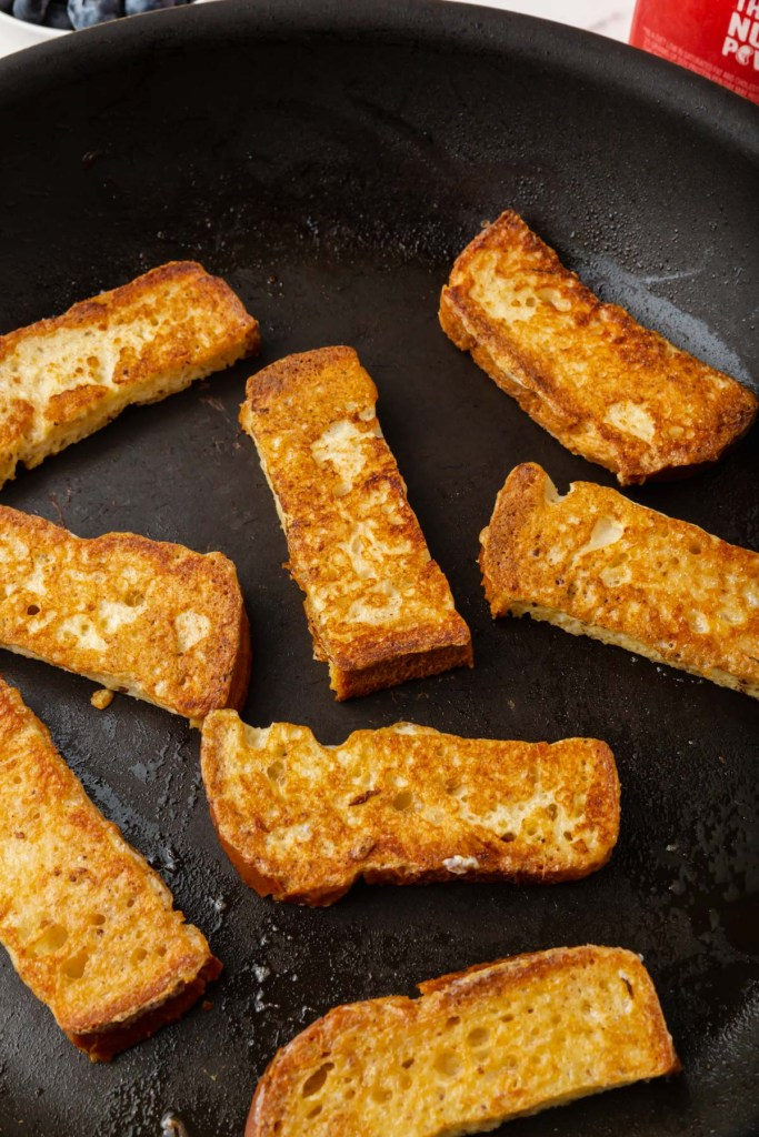 gluten-free french toast sticks cooking in a skillet and turning golden brown