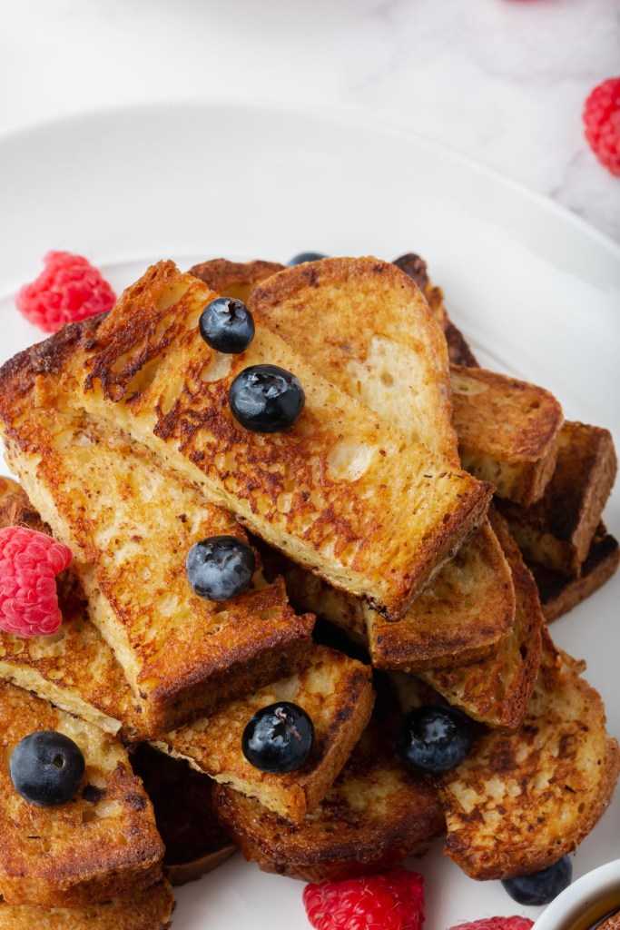 a platter with gluten-free french toast sticks and berries