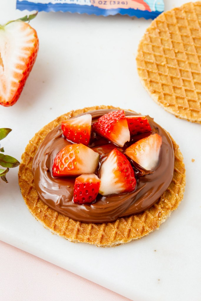 gluten-free stroopwafel covered with chocolate spread and chopped strawberries
