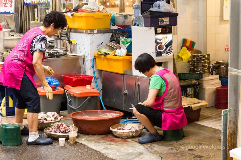 Women cleaning meat at Gwangjang Market, Seoul, South Korea