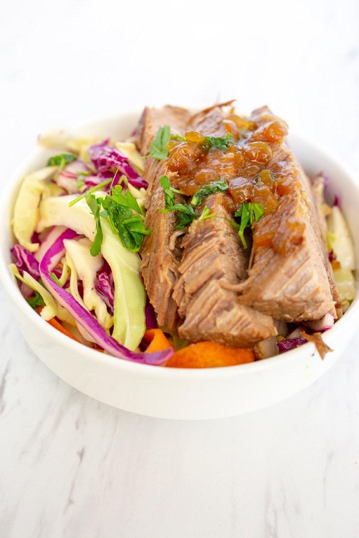 Beef Brisket served with vinegar slaw on a white bowl