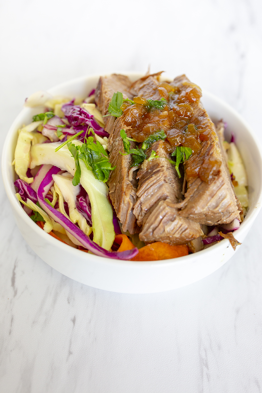 Beef brisket served with apple vinegar slaw on a white bowl