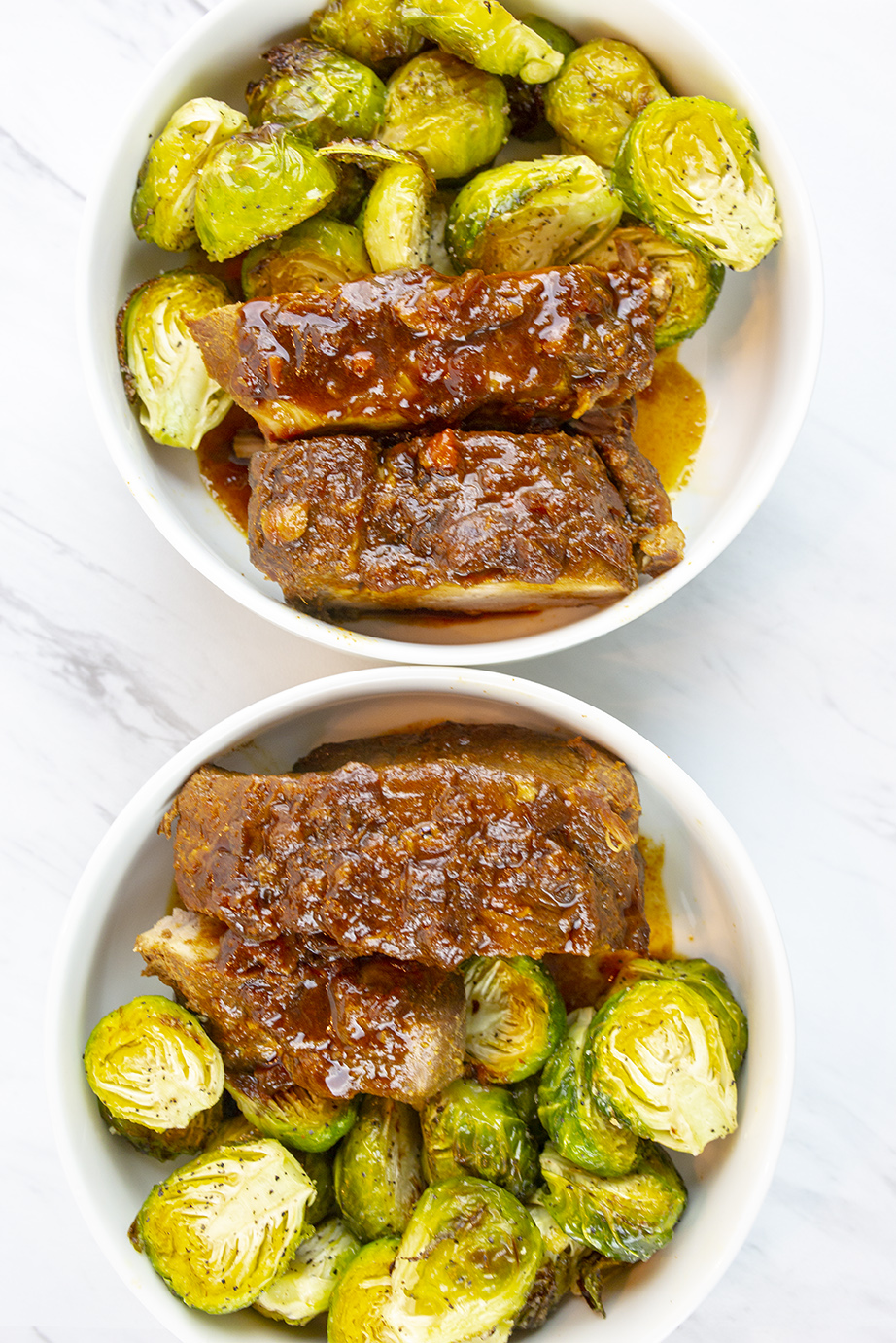 Back ribs cooked with Asian spices and served with roasted Brussels sprouts served in white bowls