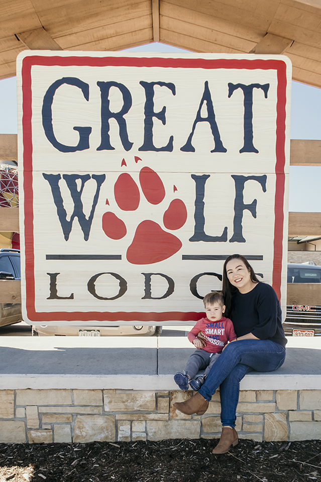 Mom and baby by the Great Wolf Lodge sign in Colorado Springs