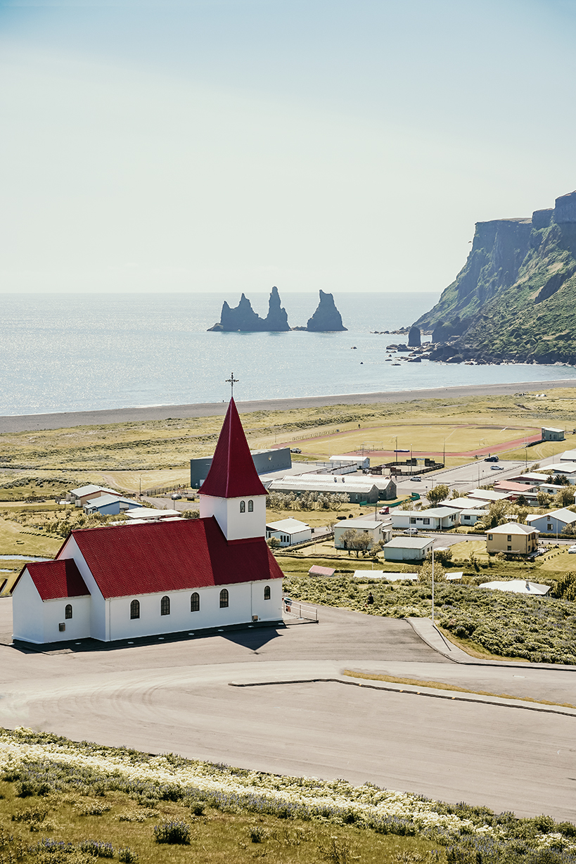 The church in the town of Vik with a view of the ocean and mountain cliffs in the background