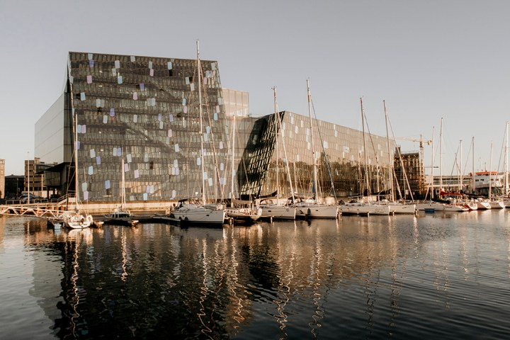Harpa Concert Hall from outside with sailing boats parked in front of it.